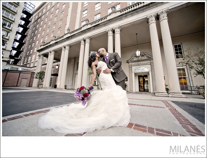 wedding_bride_groom_portrait_kiss_outside_biltmore_beautiful_white_dress_purple_red_boquette_romantic_creative_modern_ideas